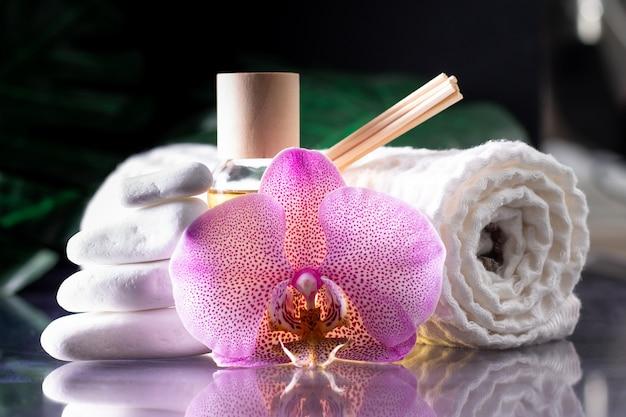 Bellissimo fiore di orchidea lilla, bottiglia trasparente di olio o profumo giallo, bastoncini di legno e asciugamano arrotolato