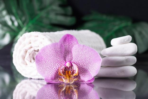 Bellissimo fiore di orchidea lilla, asciugamano arrotolato e pila di pietre bianche con foglie di monstera