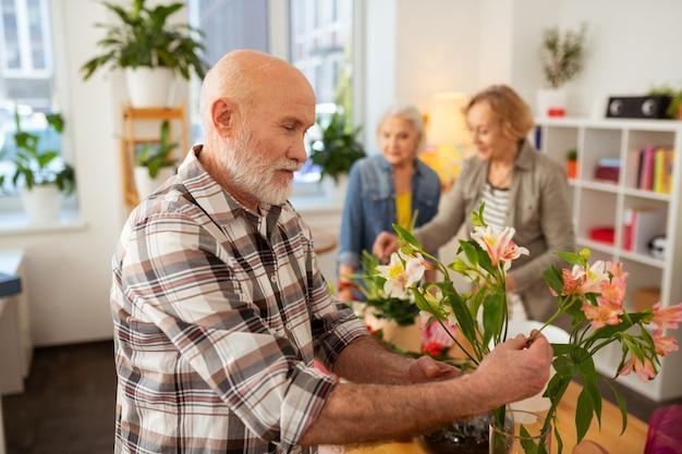 Bellissimi gigli. uomo barbuto gioioso che sorride mentre guarda i fiori in vaso