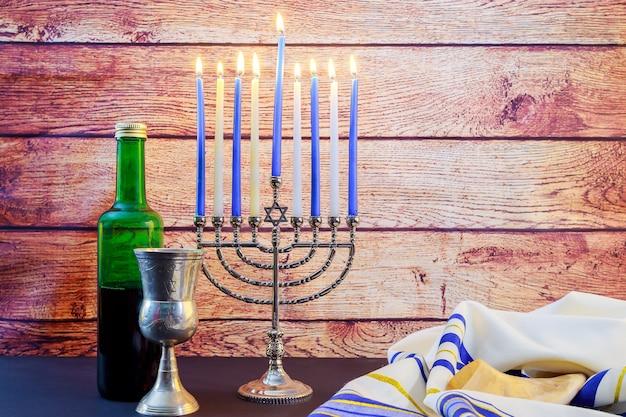 Bella menorah di hanukkah illuminata su sfondo nero. festa ebraica hanukkah vino talyt