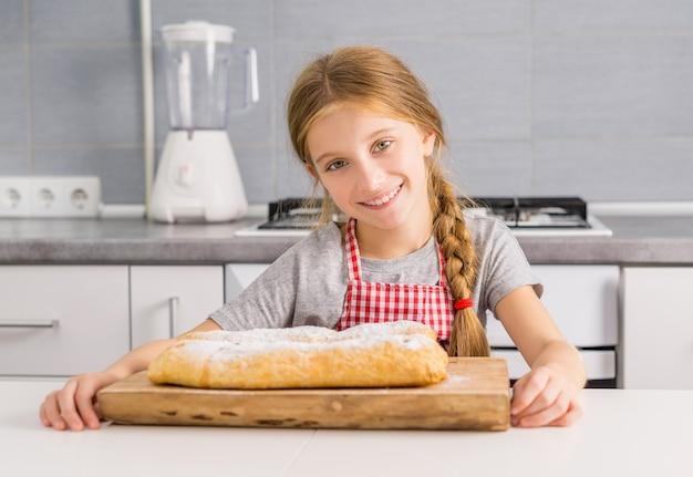 Bella ragazza litte con strudel di mele al forno sul tavolo