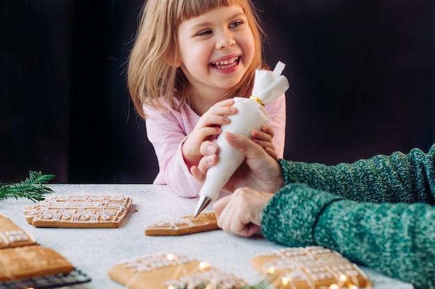 Bellissima bambina di 3 anni che sorregge sua madre che decora le case dei biscotti di panpepato di natale.