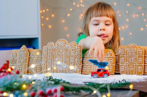 Bella bambina di 3 anni che gioca con il giocattolo dell'automobile con l'albero di natale nella città dei biscotti di pan di zenzero. messa a fuoco selettiva sulla ragazza.