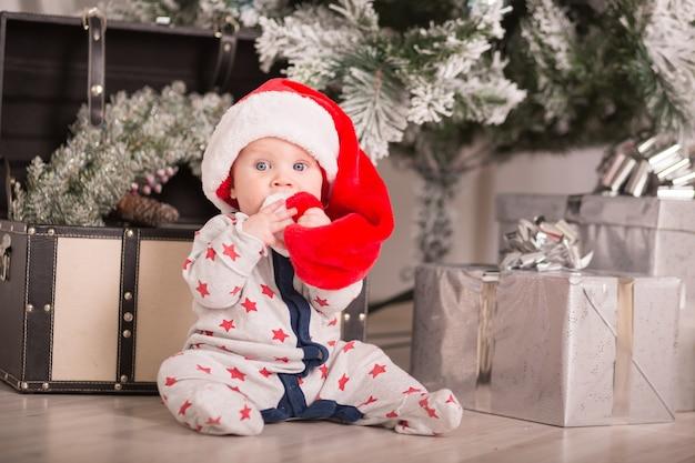 Bellissimo bambino festeggia il natale. vacanze di capodanno. bambino in costume di natale con regalo