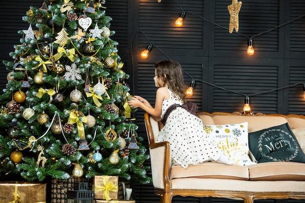 Bellissima bambina a casa per natale con albero di natale e regali