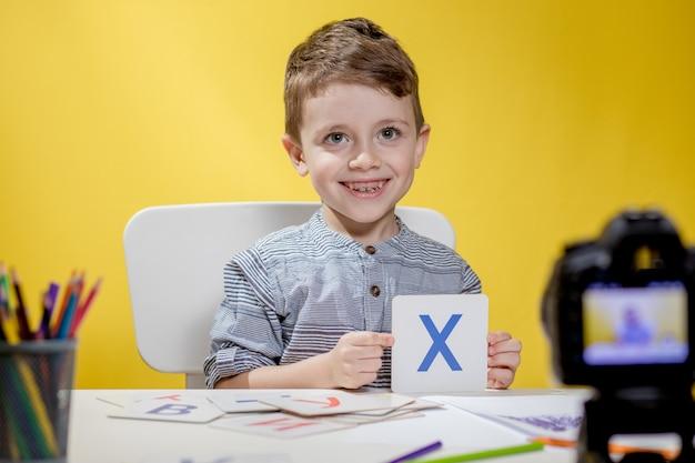 Bello piccolo blogger che si blocca sull'apprendimento dell'alfabeto su sfondo giallo