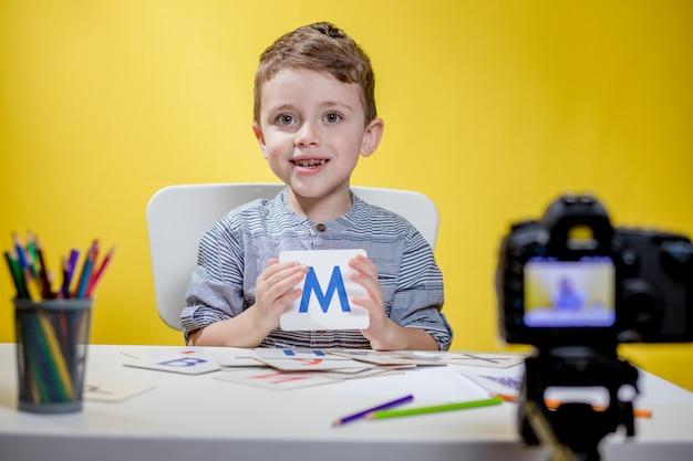 Bellissimo piccolo blogger che parla di imparare l'alfabeto