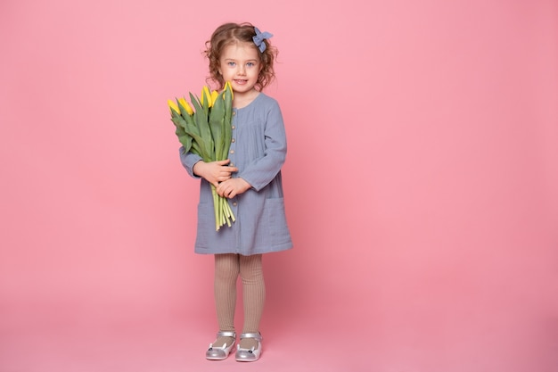 Bella bambina bionda in abito blu con bouquet di tulipani gialli su sfondo rosa con spazio per il testo.