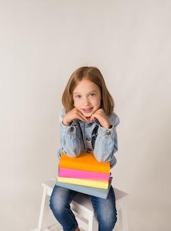 Una bella bambina bionda in denim è seduta con libri di testo su uno sfondo bianco con un posto per il testo. di nuovo a scuola