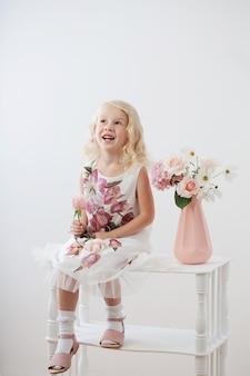 Belle piccole ragazze bionde con i fiori su fondo bianco