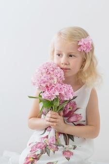 Belle bambine bionde con i fiori rosa su fondo bianco
