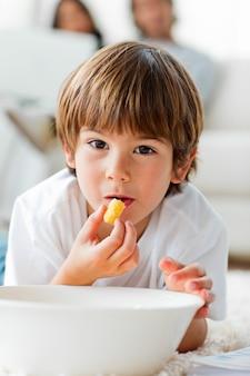 Bello ragazzino che mangia i chip che si trovano sul pavimento