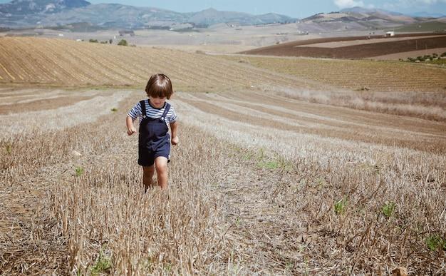 Bello ragazzino nei paesaggi rurali