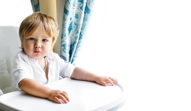 Un bellissimo ragazzino con gli occhi azzurri è seduto su una sedia bianca che mangia a casa
