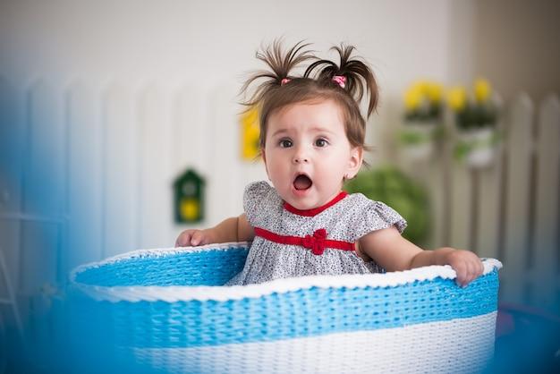 Bella bambina dagli occhi marroni si siede in un grande cestino per i giocattoli nella sua accogliente camera dei bambini.