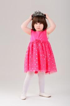 Bella bambina bruna in abito da principessa rosa con una corona su uno sfondo grigio. bel bambino