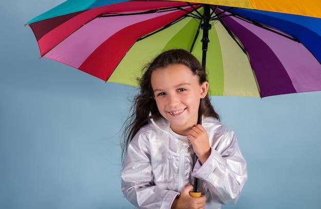 Una bella ragazza bruna sta sotto un ombrello multicolore su uno sfondo blu con un posto per il testo