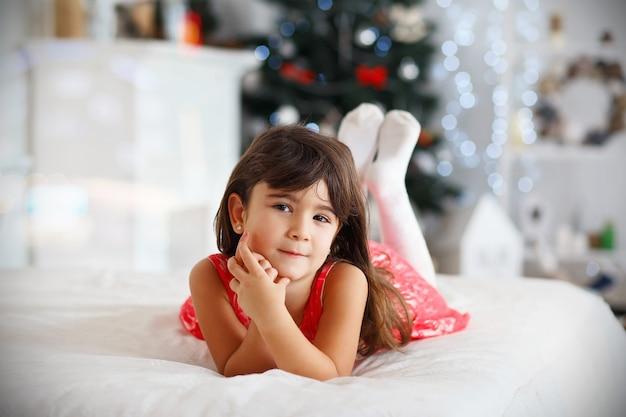 Bella piccola ragazza castana che aspetta un miracolo nelle decorazioni di natale