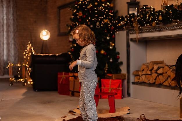 Bella bambina in pigiami alla moda sullo sfondo di decorazioni natalizie, regali e luci a casa