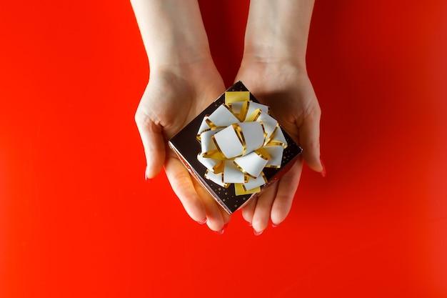 Bellissimo piccolo regalo con un nastro nelle mani di una donna su una superficie rossa. fare un regalo per le vacanze.