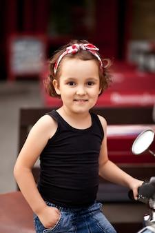 Bella bambina in stile motociclista su una moto.