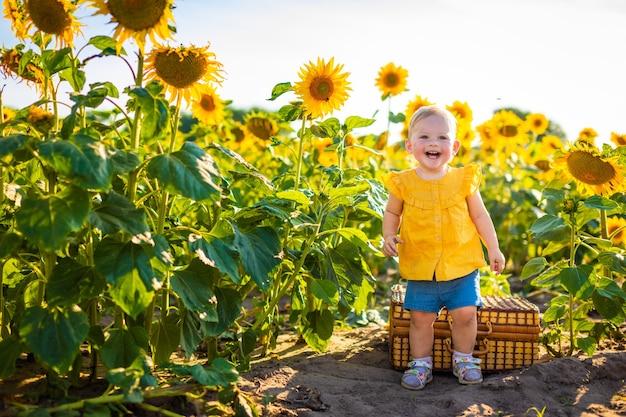 Bella bambina in un campo di girasoli in fiore in estate