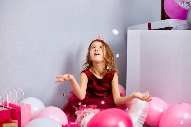 Bella bambina fa esplodere coriandoli multicolori, divertendosi alla festa di compleanno