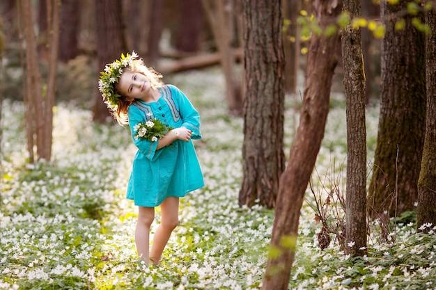 Bella bambina in un vestito blu che cammina in primavera legno. ritratto della bella ragazza con una corona di fiori sulla testa. tempo di pasqua. giardiniere sveglio che pianta le gocce di neve.