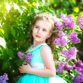 Bella bambina in un vestito blu con un grande fiocco bianco nel giardino di primavera. piccola principessa.