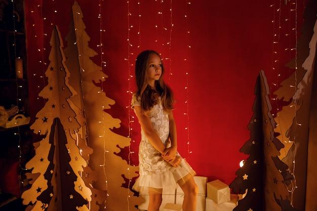 La bella bambina sogna i regali di natale. decorazioni natalizie rosse, insolite. la sera prima di natale, la vigilia di natale