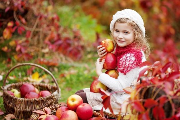 Bella bambina che tiene le mele nel giardino d'autunno. . bambina che gioca nel frutteto di mele. bambino che mangia frutta al raccolto autunnale. divertimento all'aria aperta per i bambini. alimentazione sana