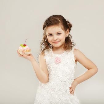 Bella bambina che tiene una deliziosa torta appetitosa con la ciliegia