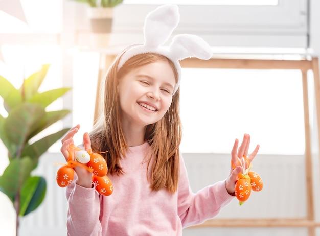 Bella bambina che tiene le uova dipinte nelle sue mani e sorride al giorno di pasqua