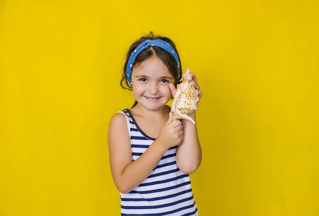 Una bella bambina che tiene una conchiglia su un muro giallo. vacanze estive.