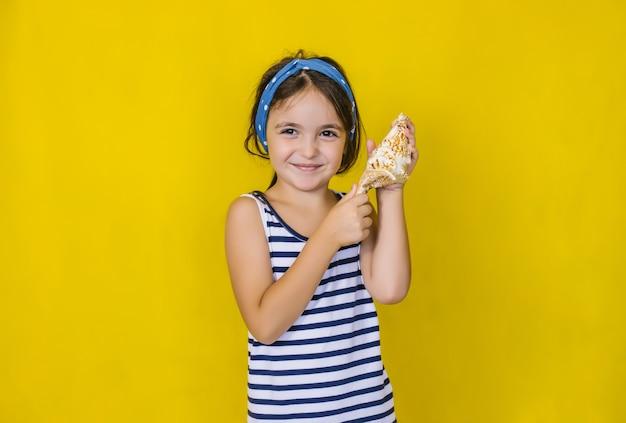 Una bella bambina che tiene una conchiglia su un muro giallo.