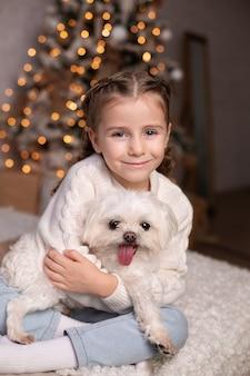 La bellissima bambina gioca con il suo cane maltese preferito a letto la vigilia di natale