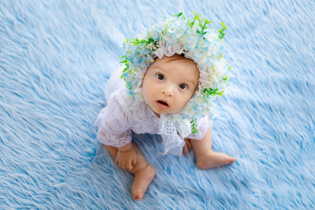 Una bella bambina si trova su un soffice tappeto blu con un cappello fatto di fiori e guarda la telecamera