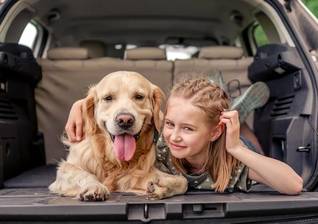 Bella bambina sdraiata con il cane golden retriever nel bagagliaio dell'auto e guardando indietro. bambino bambino con cagnolino di razza con tonque fuori nel veicolo nella natura insieme