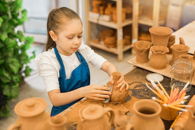 Bella bambina che fa una pentola di argilla in un laboratorio di ceramica