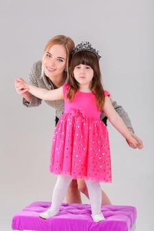 Bella bambina in abito rosa principessa con una corona e bella madre che abbraccia su uno sfondo grigio.