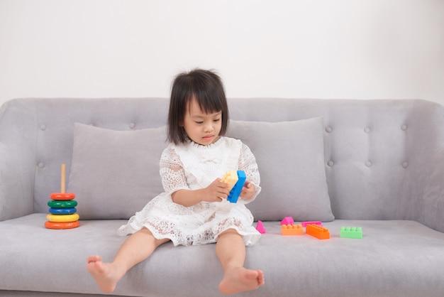Bella bambina che gioca sul divano