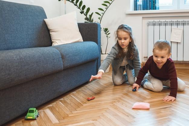 Bella bambina che gioca con il suo fratellino con le macchine sul pavimento a casa loro.