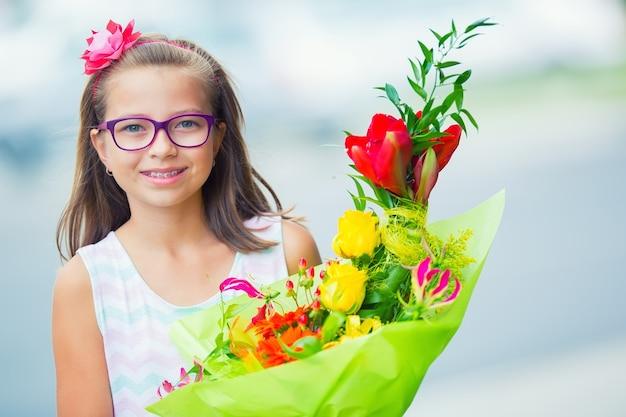 Bella bambina in posa con un grande mazzo di fiori. ragazza con bretelle e occhiali.
