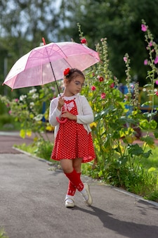 Una bella bambina in un vestito rosso e una camicetta bianca sotto un ombrello rosa si trova in una giornata estiva.