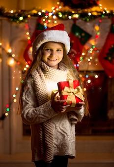 Bella bambina con cappello rosso che tiene in mano una scatola regalo scintillante