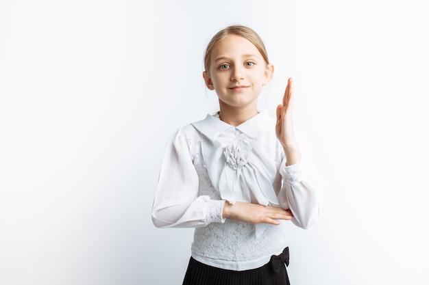 Una studentessa bella bambina, tira la mano su un muro bianco