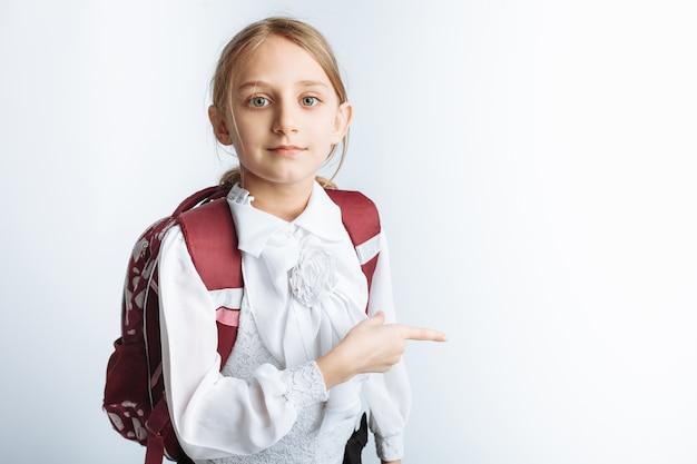 Una bella studentessa bambina con valigetta che punta a parete, muro bianco