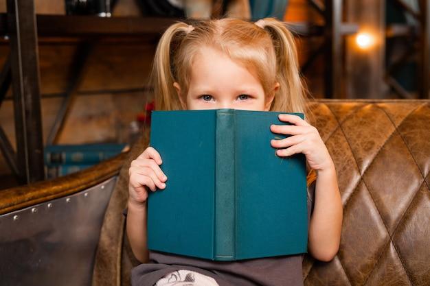 Bella bambina seduta sul divano con un libro