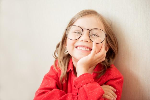 Bella bambina seduta con occhiali e vestiti rossi