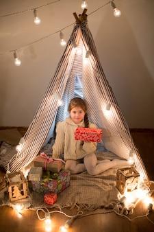 Bella bambina seduta con un regalo in mano. distribuisci la confezione regalo di natale in vacanza la sera nella bellissima sala interna. capodanno. studio.